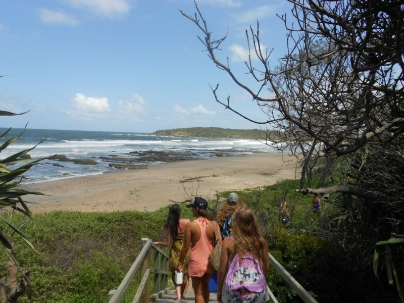 girls walking down wooden pathway to beach at mojo surf