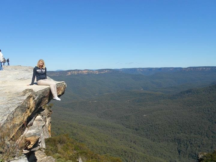 girl sitting on the edge of a cliff ledge with the blue mountains in the background