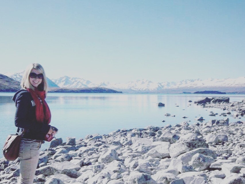 Standing next to lake tekapo in New Zealand with snow capped mountains in the background