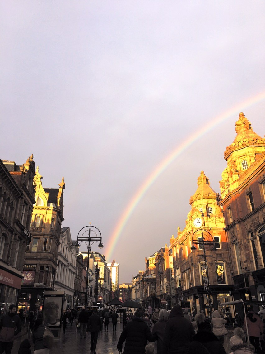 Leeds on the sunlight with a rainbow over briggate